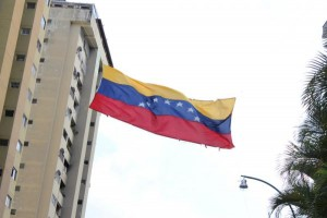 A Venezuelan flag flies in Caracas, Venezuela, during March 5, 2014, protest. Photo by GMEVIPHOTO/Shutterstock