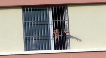 Deported migrants call for freedom from behind barred window