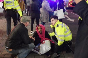 Police and a civilian aid a woman caught in a stampede from London's Oxford Street subway station on Friday after a report of gunfire prompted panicked commuters to escape the station. Police later said they found no evidence of shots fired. Photo by Facundo Arrizabalaga/EPA