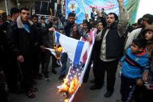 Palestinians burn portraits of President Donald Trump, and the U.S. and Israeli flag during protest against Trump's decision to recognize Jerusalem as Israel's capital in Rafah the southern Gaza on Friday. Photo by Ismael Mohamad/ UPI. | License Photo
