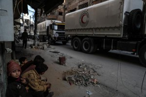 Children sit and watch a convoy of Syrian Arab Red Crescent trucks as they arrive in Douma, in Eastern Ghouta, Syria. Photo by Mohammed Badra/EPA-EFE