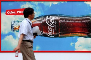 A man carrying a can of Coca-Cola walks past a Coca-Cola advertisement in downtown Tokyo, Japan. The drink maker has said it plans to create a low-alcohol canned drink for Japan markets. File Photo by Adny Rain/EPA-EFE