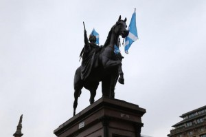 A statue in George Square is covered in the Scottish flag on September 18, 2014. This week, the Scottish government released figures that show 19 percent of its population is living in poverty. File Photo by Hugo Philpott/UPI | License Photo