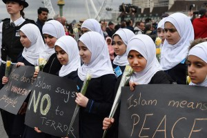 Muslim children carrying flowers join with London police officers and members of the public as they hold a vigil on Westminster Bridge in central London on March 29, 2017, one week after the Westminster terror attack. File Photo by Andy Rain/EPA