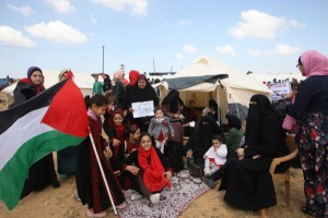 A family sits by tents pitched by Palestinians on the Gaza border with Israel during a protest in Rafah, Southern Gaza on Friday. File Photo by Ismael Mohamad/UPI. | License Photo
