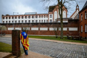 Catalonia sympathizer Eduardo Alonso has an Catalan flag wrapped around his shoulders as he stands in the front of the Justizvollzugsanstalt Neumuenster prison, where former Catalan leader Carles Puigdemont is detained, in Neumuenster, Germany, on Thursday. Photo by Jens Schlueter/EPA-EFE