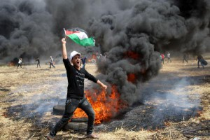 A Palestinian man holds his national flag as others burn tires to protect themselves from shots of Israeli soldiers at the Israel-Gaza border on Friday. A video from a few months ago shows Israeli snipers cheering as a Palestinian man is shot on the border. Photo by Ismael Mohamad/UPI | License Photo