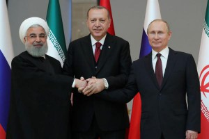 Turkish President Recep Tayyip Erdogan (C), Russian President Vladimir Putin (R) and Iranian President Hassan Rouhani (L) join hands as they pose for a photo during their meeting at the Presidential Palace in Ankara, Turkey, on Wednesday. Photo by Mikhail Klimentyev/EPE-EFE