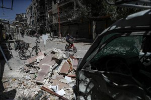 People make their way through destroyed streets in Douma, Syria, March 26, 2018. At least 27 people have been killed in airstrikes there Friday. Photo by EPA-EFE/Mohammed Badra