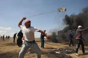 A Palestinian youth uses a slingshot to hurl stones during clashes along the Gaza-Israel border Friday. Photo by Ismael Mohamad/UPI | License Photo
