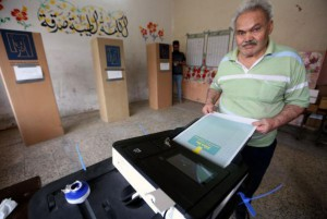 An Iraqi man casts his ballot during the parliament elections Saturday at a polling station in Baghdad. For the first time, voting was conducted electronically. Photo by Ali Abbas/EPA