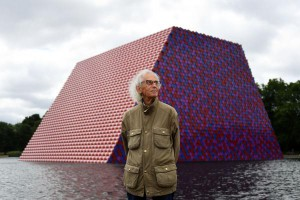 "Bulgarian artist Christo stands in front of his artwork ""The London Mastaba"" built on the Serpentine Lake in London on Monday. Photo by Andy Rain/EPA-EFE"