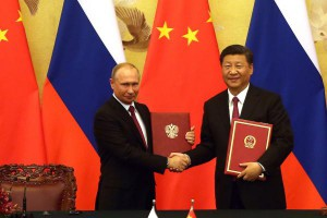 Russian President Vladimir Putin (L) and Chinese President Xi Jinping exchange trade agreements at a signing ceremony in Beijing on Friday. The two leaders agreed peace and stability in Northeast Asia is in their mutual interests, according to Russian press reports. Photo by Stephen Shaver/UPI | License Photo