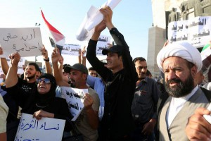 Iraqis carry banners and chant slogans during a demonstration at Tahrir square in central Baghdad, Iraq, on Friday. Two days laters, protesters tried to storm the main provincial government building in Basra. Photo by Ahmed Jalil/EPA