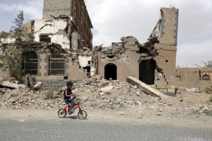 A child rides a bicycle past a destroyed building leveled by a coalition airstrike in Sanaa, Yemen, on June 27. A bombing in Yemen Thursday is one of hundreds the coalition has carried out this summer. File Photo by Yahya Arhab/EPA-EFE