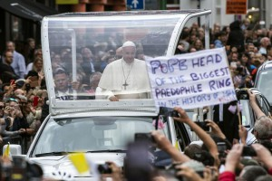 A protestor holds up a banner while Pope Francis is driven in his Pope mobile through the streets of Dublin, Ireland, Saturday. Photo by Will Oliver/EPA-EFE