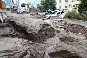 Mud covers vehicles on a destroyed street after a powerful earthquake and liquefaction in Sapporo, Hokkaido, northern Japan, on Thursday. Several people died and dozens were reported missing, officials said. Photo by Jiji Press/EPA-EFE