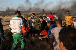 Palestinian protesters carries a wounded man away from the scene of clashes with Israeli forces during protest at the Israel-Gaza border in Rafah. Photo by Ismael Mohamad/UP | License Photo