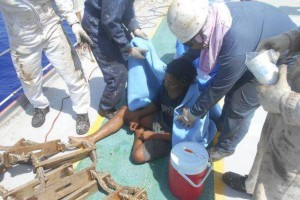 Aldi Novel Adilang (C) is given water aboard a Panamanian shipping vessel on August 31 after being adrift in the Pacific Ocean for 49 days. Photo courtesy of Indonesian Consulate in Osaka, Japan/Facebook