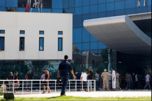 Libyan firefighters and security personnel stand in front of the National Oil Corporation in Tripoli Monday following a violent attack by terrorists. Photo by EPA-EFE