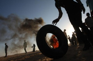 Palestinian protesters drag burning tires during a demonstration at the Israel-Gaza border in Rafah, in the southern Gaza Strip on August 10. Weekly Friday protests have been held since late March. File Photo by Ismael Mohamad/UPI | License Photo