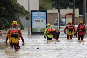 Firefighters wade through several feet of water Monday to rescue people trapped by flash floods in Trebes, France. Photo by Guillaume Horcajuelo/EPA-EFE