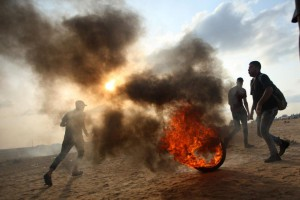 ِA Palestinian protester drags a burning tire during a protest in the Gaza Strip on October 19. Protests Friday left four Palestinians dead. Photo by Ismael Mohamad/UPI. | License Photo