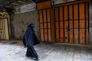 A Palestinian woman walks past closed shops during a general strike Monday against Israel's Nation State Law, which declares that only Jews have the right of self-determination in Israel. Photo by Debbie Hill/UPI | License Photo
