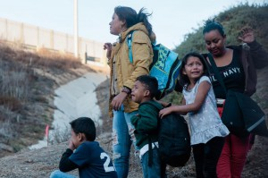A migrant family looks at the border fence that divides the United States and Mexico near Las Playas de Tijuana, Mexico, after jumping the fence to enter the United States at San Ysidro, Calif., on December 2. Photo by Ariana Drehsler/UPI | License Photo