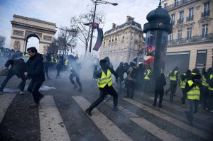 A yellow vests protester hurls an object at police forces during a demonstration in Paris, France, Saturday. Photo by Julien De Rosa/EPA-EFE