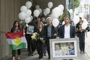 Tima Kurdi (holding flowers), her husband Rocco Logozzo (R) and other mourners hold a memorial in Vancouver for her family members, refugees who died trying to leave Syria, September 5, 2015. Canada's immigration ministry said it plans to admit more than 1 million immigrants, including thousands of refugees, over the next three years. File Photo by Heinz Ruckemann/UPI | License Photo