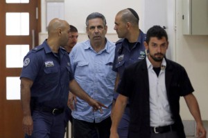 Gonen Segev (C), a former Israeli cabinet minister indicted on suspicion of spying for Iran, is escorted by prison guards as he arrives at court in Jerusalem July 5, 2018. Photo by Ronen Zvulun