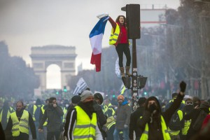 A woman wearing a yellow vest, as a symbol of protest against higher fuel prices, waves a French flag during clashes with police on Paris' Champs Elysee in November. File Photo by Christophe Petit Tesso