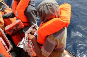 A migrant woman sits aboard a rubber dinghy of rescue ship Aquarius off the Libyan coast on March 31, 2018. A dinghy capsized on Saturday, killing more than 100 migrants off Libya. File photo by Javier Martin