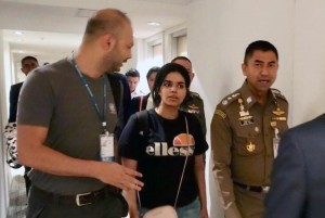 Rahaf Mohammed Al-qunun (C) walks with Thai Immigration Police Chief Surachet Hakparn (R) at a transit hotel inside Suvarnabhumi International Airport in Bangkok, Thailand, Monday. Photo by Thai Immigration Bureau/