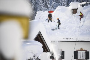 Workers clear a roof in Gerold, Germany, Friday. Austria and southern Germany have received heavy snowfalls in the past days. Photo by Philipp Guelland