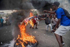 Protesters participate in an anti-government rally in Port-au-Prince, Haiti, including burning an American flag. During a week of protests, demonstrators have called for the resignation of President Jovenel Moise. Photo by Jean Marc Herve