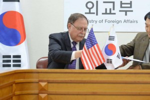 Timothy Betts (L), the U.S. negotiator for defense costs in South Korea, and his counterpart, Chang Won-sam sign a provisional cost-sharing deal during their meeting at the Ministry of Foreign Affairs in Seoul on Sunday. Photo by Yonha