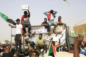 Demonstrators celebrate Thursday as they head towards the army headquarters amid rumors President Omar al-Bashir was removed from power.